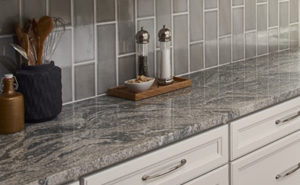 Gray granite countertop with tile backsplash and white cabinets